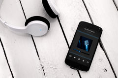 Smartphone moderno en el tablero de madera con los auriculares del bluetooth Imagenes de archivo