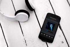 Smartphone moderno sul bordo di legno con le cuffie del bluetooth Immagini Stock