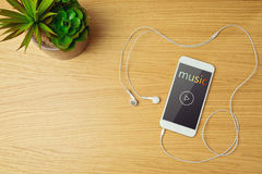 Smartphone with music app on wooden table. Stock Images