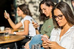 Smartphone nałóg wśród żeńskich uczni obraz stock
