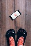 Smartphone na drewnianej drewnianej podłoga Czarny Piątku ogłoszenie Kobieta cieki w kotów kapciach, pasiaste skarpety Odgórny wi obraz stock