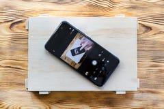 Smartphone na drewnianym pudełku z ja wizerunek na ekranie Daleki kamery kontrola zastosowania pojęcie zdjęcia stock