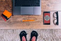 Smartphone na drewnianym stole Czarny Piątku ogłoszenie Odgórny widok Kobieta cieki w kotów kapciach, pasiaste skarpety fotografia royalty free