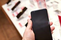 Smartphone na mão de um homem em uma loja da eletrônica fotos de stock