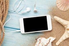 Smartphone na madeira e na areia do mar com estrela do mar e shell Fotos de Stock Royalty Free