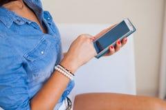 Smartphone nas mãos da mulher Foto interna fotos de stock royalty free