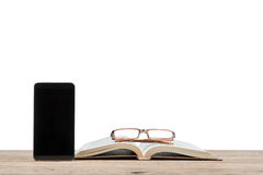 Smartphone near the book and glasses Stock Photos