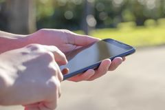 Smartphone negro a disposición en el parque en el aire abierto, encendido por el sol fotos de archivo libres de regalías