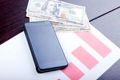 Smartphone negro en la carta de crecimiento, al lado de varias cuentas de d Foto de archivo