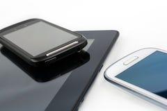 Smartphone negro en la tableta negra con el móvil blanco además Foto de archivo
