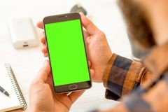 Smartphone nero con lo schermo verde per la tenuta compositing chiave della mano di intensità per la carta online compositing chi immagine stock libera da diritti
