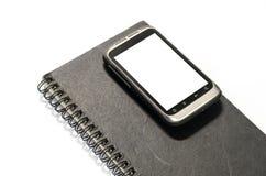 Smartphone no livro de nota Imagens de Stock