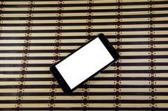 Smartphone noir sur un tapis en bambou photographie stock libre de droits