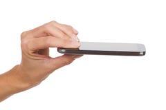 Smartphone nos dedos da mulher Foto de Stock Royalty Free