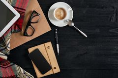 Smartphone with notebook and cup of coffee on wooden background. Cell phone with writing set with espresso. Smartphone with notebook and cup of coffee on wooden Royalty Free Stock Image