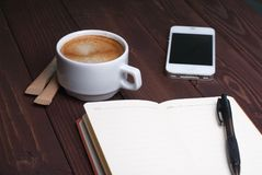 Smartphone with notebook and cup of strong coffee on wooden background. Cell phone with writing set with espresso Stock Photo