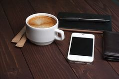 Smartphone with notebook and cup of strong coffee on wooden background. Cell phone with writing set with espresso Stock Photos