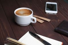 Smartphone with notebook and cup of strong coffee on wooden background. Cell phone with writing set with espresso Royalty Free Stock Photography