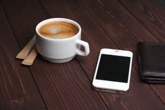 Smartphone with notebook and cup of strong coffee on wooden background. Cell phone with writing set with espresso Royalty Free Stock Photo