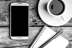 Smartphone with notebook, fountain pen and cup of coffee. Royalty Free Stock Images
