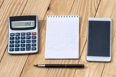 Smartphone with notebook, pen  and calculator. On wooden table Stock Image