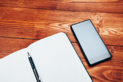 Smartphone and notebook with pen Stock Photo