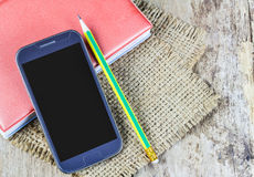 Smartphone,notebook and pencil on wooden table Stock Image
