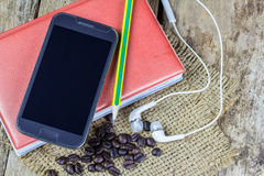 Smartphone,notebook,and pencil on wooden table Stock Photos