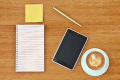 Smartphone notebook stickers and coffee cup on wooden desktop.3D. Illustration Stock Photo