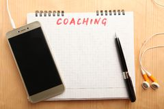 Concept coaching online. Smartphone and notebook on a wooden background. Concept coaching online royalty free stock photo