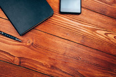 Smartphone and notebook on wooden table Royalty Free Stock Image