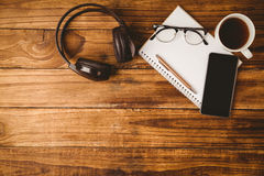Smartphone on notepad next to cup of coffee and music headphone Royalty Free Stock Images