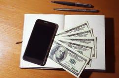 Smartphone, notepad, pieniądze Fotografia Royalty Free