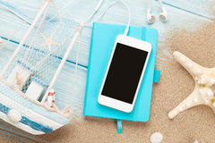 Smartphone and notepad on sea sand with starfish and toy boat Royalty Free Stock Photography