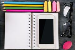 Smartphone, Notizblock und Versorgungen Stockbild