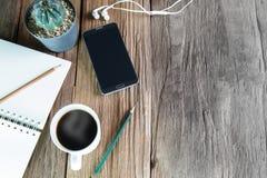 Smartphone, Notizbuch, Bleistifte, Kopfhörer, Topf des Kaktus und Tasse Kaffee auf hölzernem Hintergrund der Weinlese Stockfoto