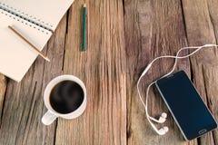 Smartphone, Notizbuch, Bleistifte, Kopfhörer und Tasse Kaffee auf hölzernem Hintergrund der Weinlese Stockbilder