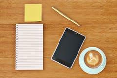 Smartphone-Notizbuchaufkleber und Kaffeetasse auf dem hölzernen Desktop 3d Stockfoto