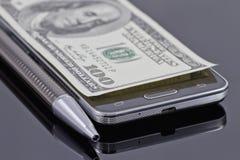 Smartphone novo, pena de esferográfica e cem dólares Foto de Stock