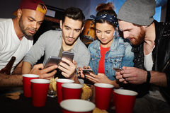 Smartphone Obsession at Night Club Party. Friends looking at smartphones during meeting party in night club Stock Image