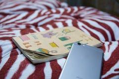 Smartphone och anteckningsbok på en kramkudde Arkivbild