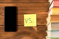 Smartphone och en bunt av b?cker p? en tr?tabell Begreppet av att f? information fr?n b?cker eller internet arkivfoto