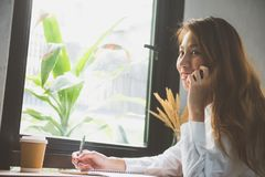 Smartphone och kopp kaffe för asiatisk kvinna talande Freelancer som arbetar i coffee shop Student som direktanslutet lär Arkivbilder