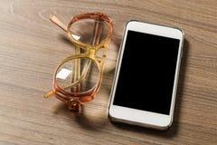 Smartphone och läsningexponeringsglas på ett gammalt träbräde royaltyfria foton