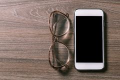 Smartphone och läsningexponeringsglas på ett gammalt träbräde arkivbilder