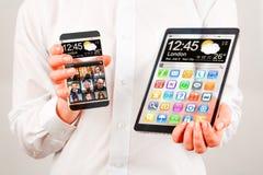 Smartphone och minnestavla med den genomskinliga skärmen i mänskliga händer. Arkivbild
