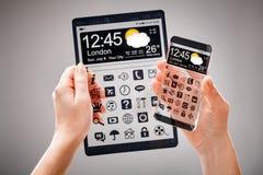 Smartphone och minnestavla med den genomskinliga skärmen i mänskliga händer Royaltyfri Foto