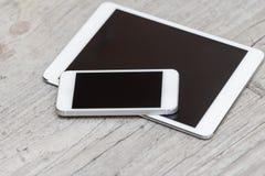 Smartphone och minnestavla på den gråa träbakgrunden Arkivfoto