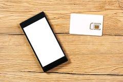 Smartphone och SIM-kort på kontorstabellen, bästa sikt Royaltyfria Foton