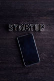 Smartphone och startar upp tecknet som göras av kakaskärare Royaltyfri Foto